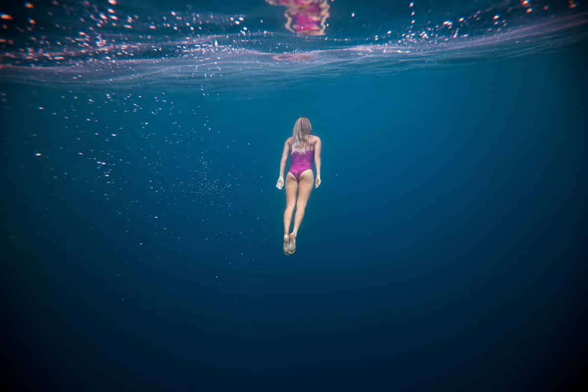 Surferin unter Wasser in pinken Bikini
