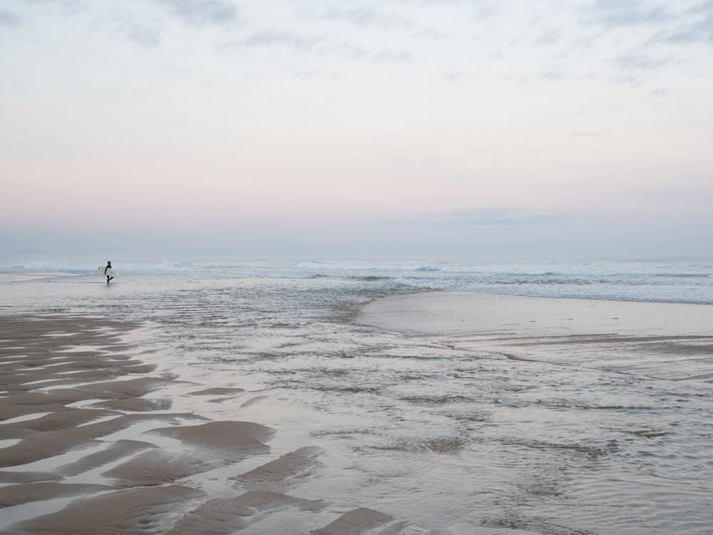 Surferin beim Sonnenaufgang