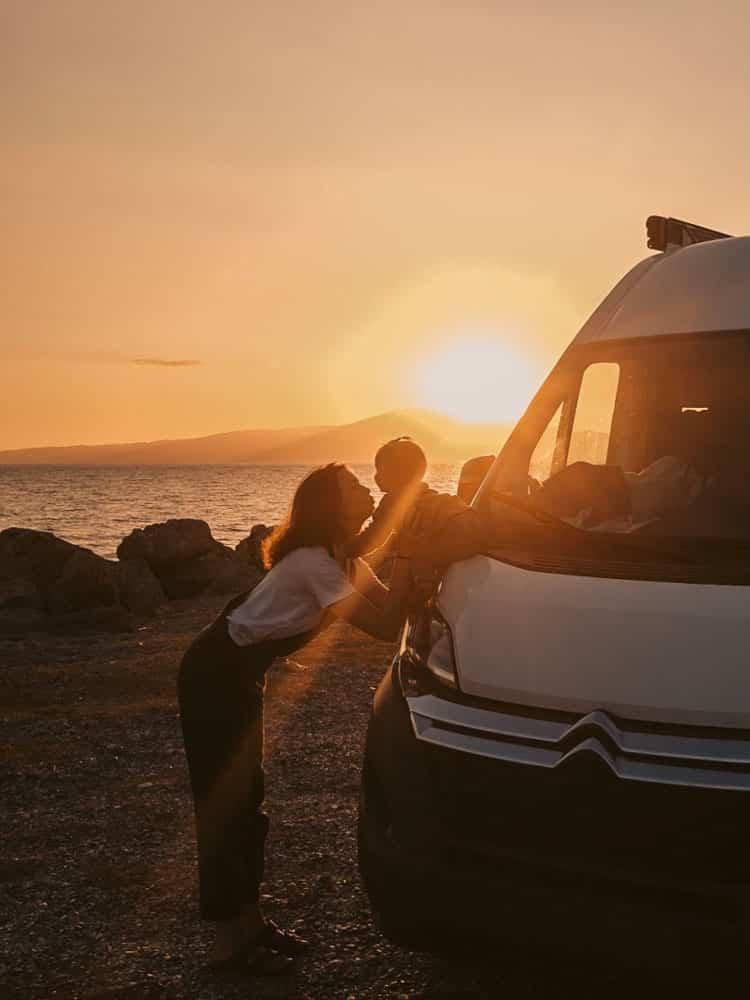 Mutter mit Baby vor Van, Sonnenuntergang