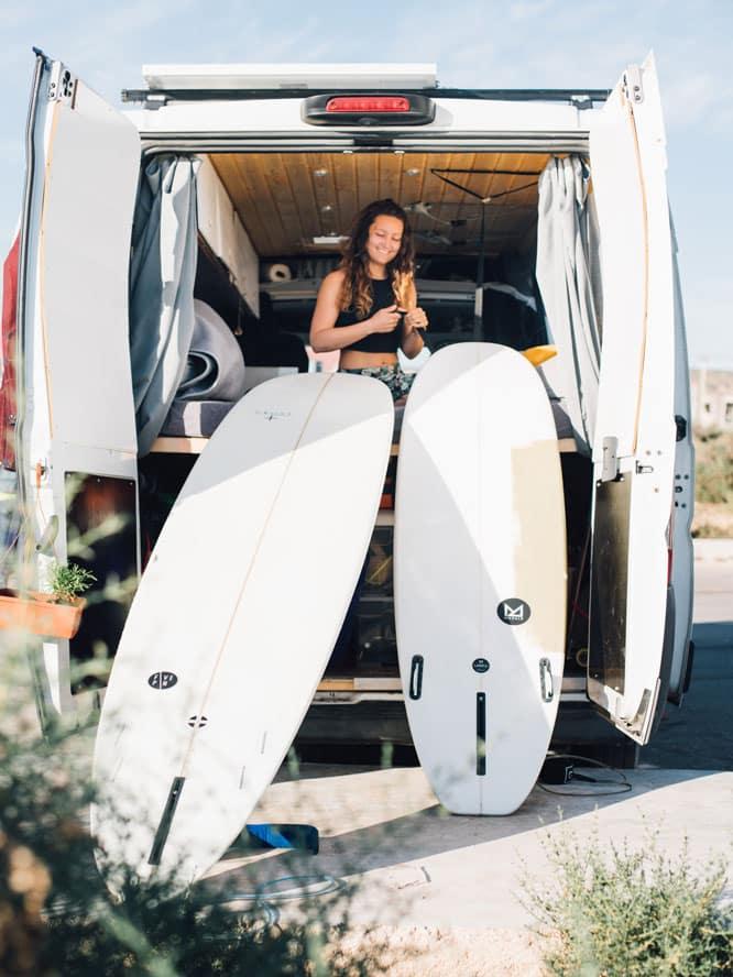 Frau in Van mit zwei Surfboards