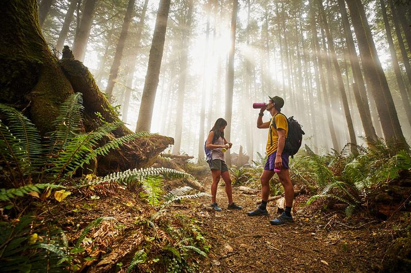 Paar im Wald mit Hydro Flask Trinkflaschen